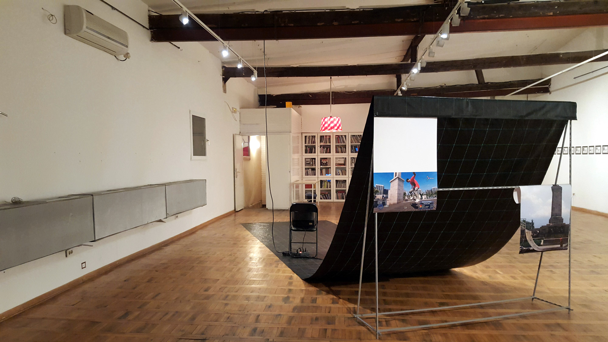 exhibition view, A Direct Model for Physical Action (2 monitors, 2 inkjet prints, plastic foil, metal, chair, wood)